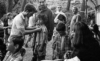 Groupe d'enfants et d'adultes le matin pendant les préparatifs du tournage, maquillage, habillage, pose de micro. La costumière et le réalisateur sont présents.