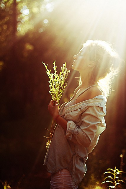 girl in sunlight holding flower