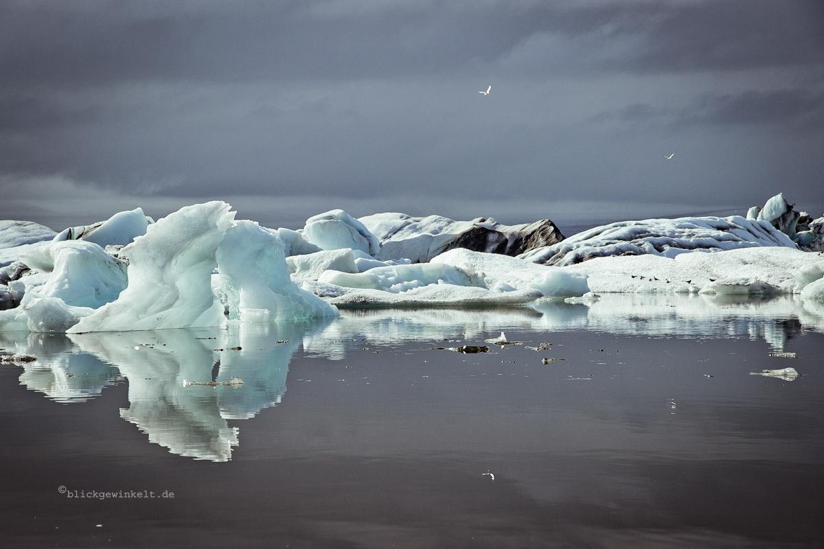 Eisberge spiegeln auf stillem Wasser vor grauem Himmel