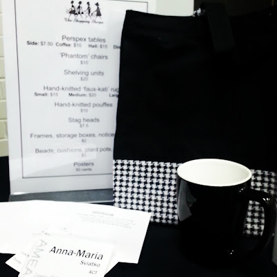 Black and white bag and mug on a sales table at a conference, with a conference badge in the front.