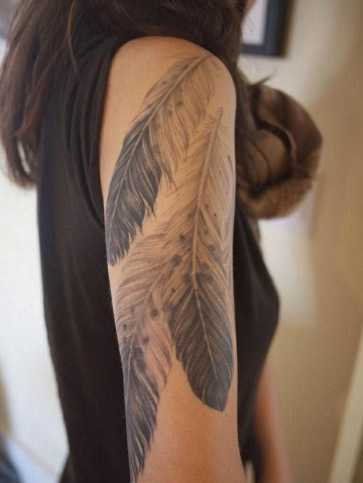 vemos una chica con un tatuaje en su brazo, el tatuaje de plumas le cubre media manga