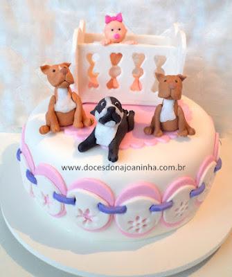 Bolo decorado Chá de Bebê com o bebê no bercinho, nome na lateral do bolo e decorado com cachorrinhos, detalhes em branco, lilás e rosa com bordado Inglês na decoração.