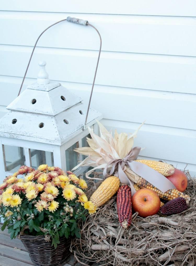 Zimtstangen, Kerzenlaterne, orange Chrysanthemen und Kürbis