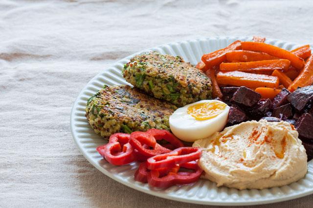 Povrćne polpete od kinoe sa spanaćem i fetom, poslužene uz pečeno povrće, humus i meko kuvano jaje