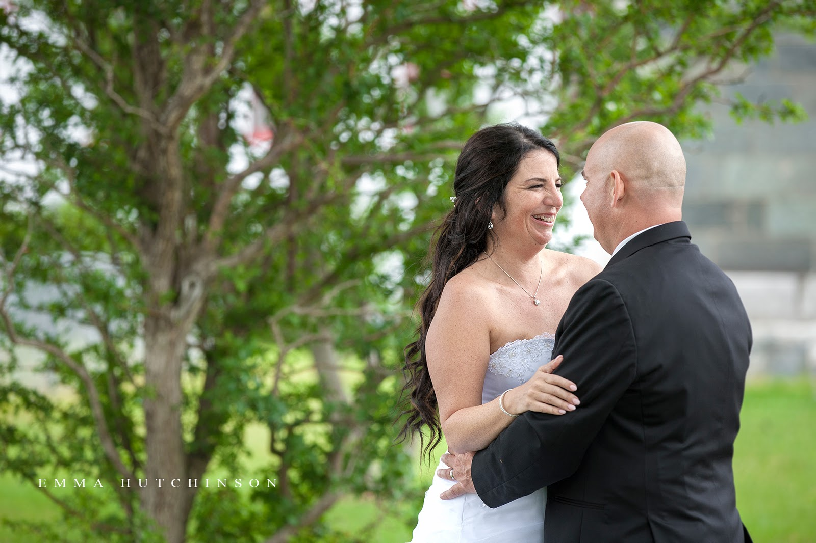 Candid wedding photography - bride and groom laughing.