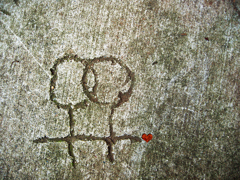 A drawing of two stick-figures holding hands with a red love heart, drawn into wet cement