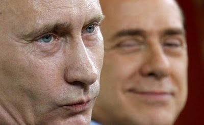 Vladimir Putin and - in the background - his admirer, Silvio Berlusconi