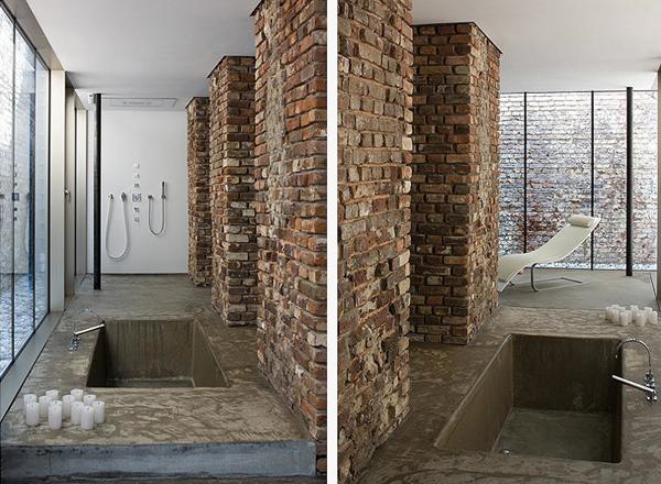 Minimalistyczna łazienka beton, cegła i biała ściana z panelem prysznicowym  wpuszczana wanna w podłogę betonową