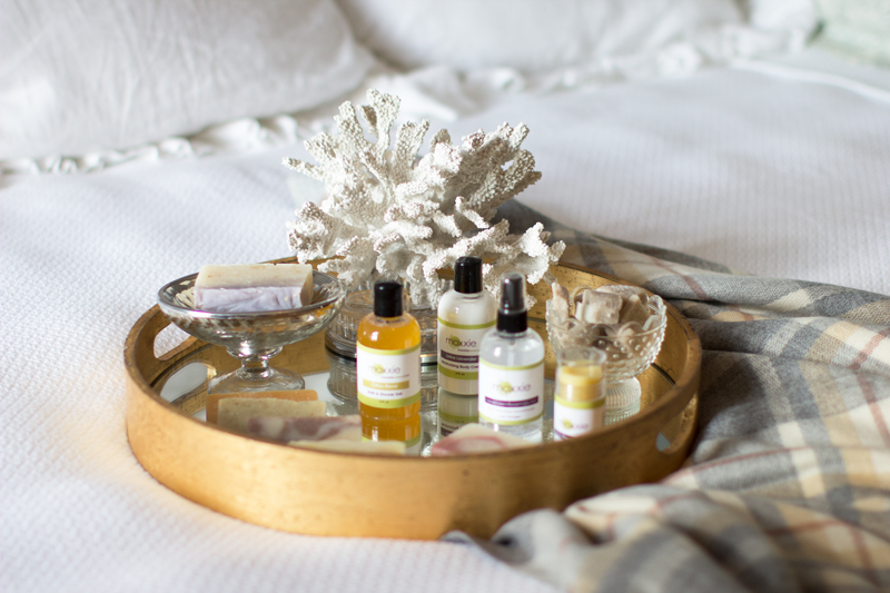 natural bath products, gold mirrored tray, plaid blanket scarf