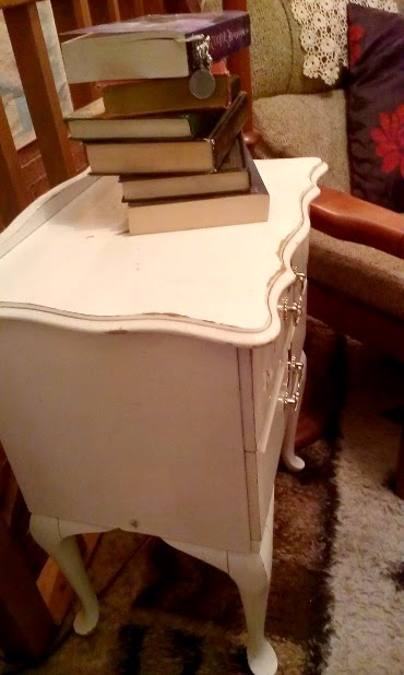 Small white vintage bedside table next to a reading chair, with a pile of books on top.