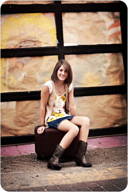 Oro Valley teen sits on stool in an urban setting during senior portrait session