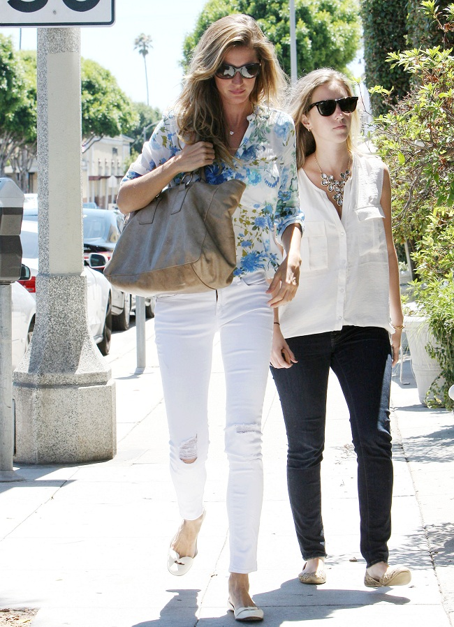 Gisele wearing ripped denim skinnies and a floral blouse