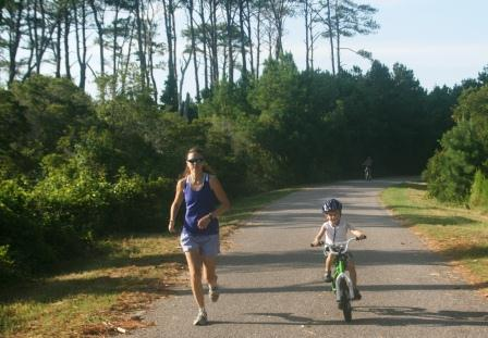 Mother and son running and biking (respectively) the wildlife loop in early morning