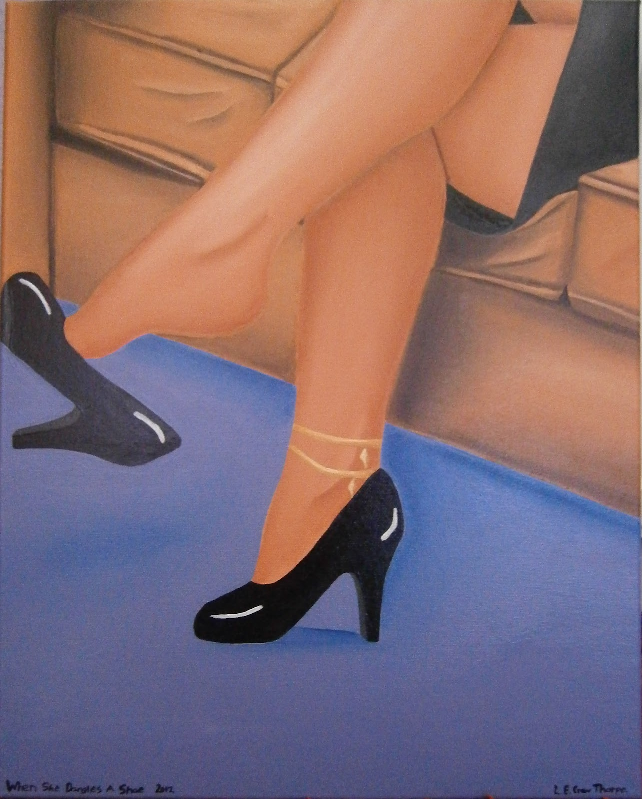 A girl sitting on a couch with her legs crossed dangling a shoe