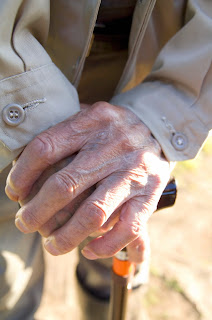 Elderly man's hands resting on a cane.