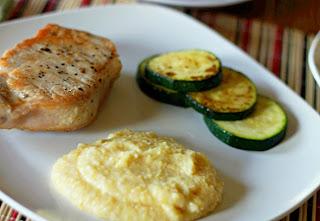 creamy polenta, pork chop and zucchini on white plate