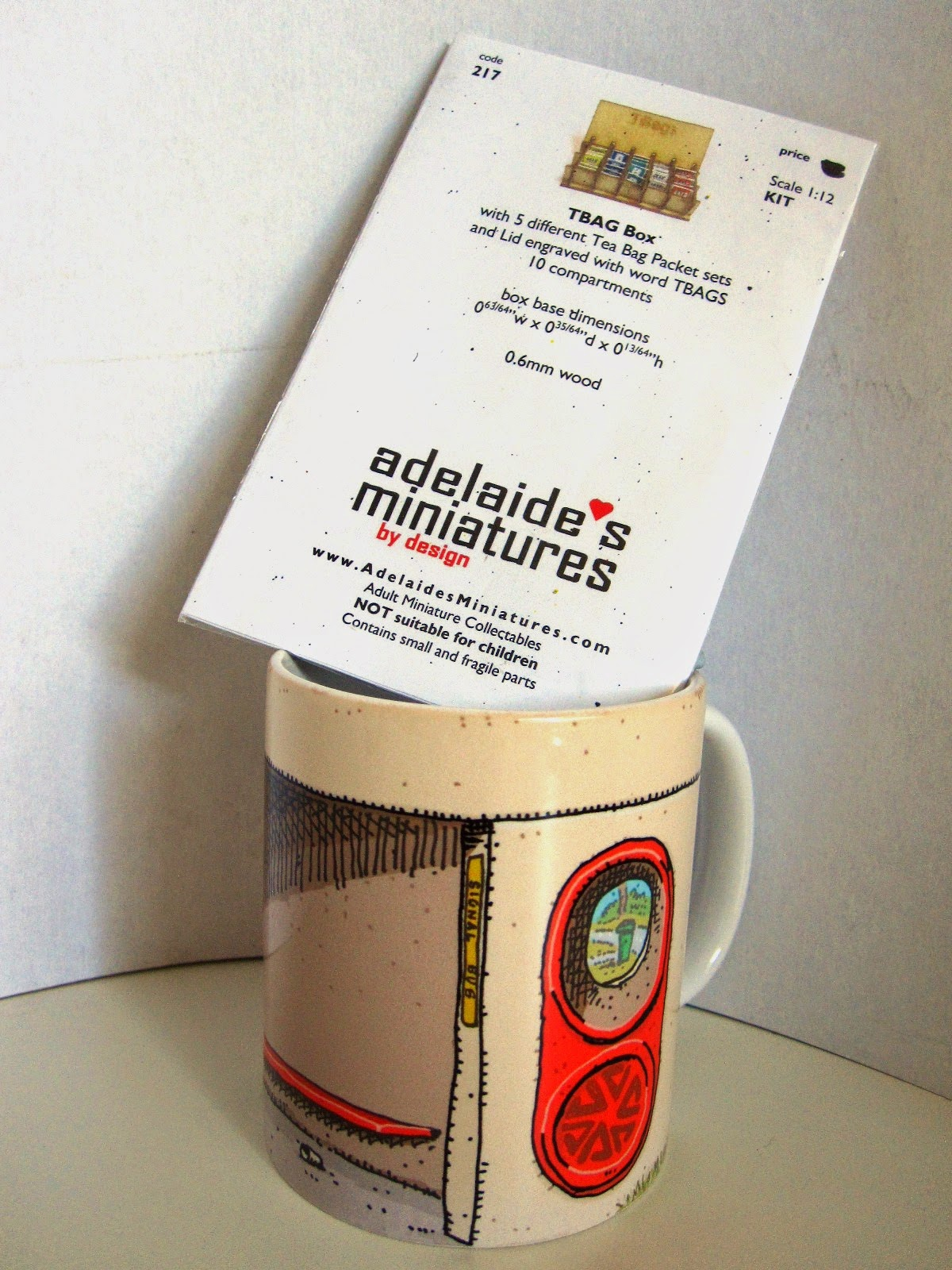 Trevor Dickinson Canberra bus shelter mug with miniature tea bag box kit sticking out of it.