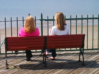 Two women sitting on a bench.