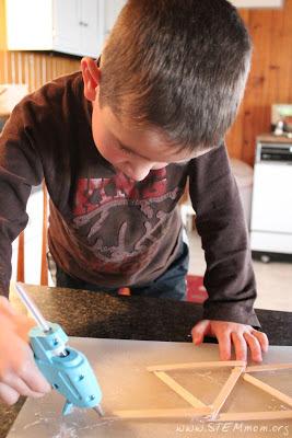 Kindergartner with glue gun: Building his first bridge out of popsicle sticks: STEMmom.org