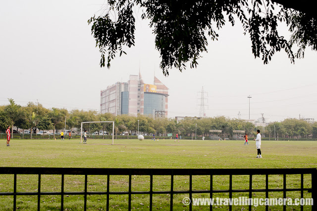 Noida is one of the top revenue generating city for Uttar Pradesh state of India and is mainly known as one of the software hubs in India !!! In the middle of Noida city, there is a Sports stadium for residents of city and really popular among children !!!My office is near to Noida Stadium and it comes on the way from my house to office... Two years back, an area of this stadium was developed for golf lovers... It's just in front main gate and can be seen by everyone crossing through road touching SPICE mall and Adobe India office...There is a wonderful football ground inside Noida Stadium.... Coaches for various sports are available at Noida Stadium and school children come here during early mornings & evenings... People from surrounding sectors like 21, 25 and 26 come for jogging...Tennis, basketball and squash are also available... There are different models to get entry to Noida stadium. It seems, there is some long term membership where some amount needs to be submitted for an year or so. For that you get access to various parts of the stadium and mentors can be identifies for improving your skills... Other way is to get membership for a month or so... One of my friend used to go there and he was only allowed to access badminton ground for one hour a day ! Stadium is very well maintained and recently I have heard that huge amount is approved by UP government for improving facilities at Noida Stadium... Annual Flower Fair of Noida takes place at this stadium only !!All grounds for various sports are well connected with roads and parking areas are there in surroundings... There are appropriate jogging paths at Noida Stadium !!Noida Stadium is adjacent to jalvahu vihar, Sector 21, 25,22, spice mall and city center. The sectors you see behind this ground are in sector 21...Honda City parked in parking area of Noida Stadium !! And the building behind if Adobe Systems India... The most colorful and beautiful building in Noida City... This is back side of the building which is black and grey... Front part is really colorful and has wonderful colors...