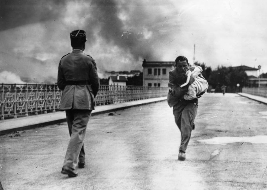 A journalist dashes across a bridge between to rescue a baby during Civil War. [1936] - The 63 Most Powerful Photos Ever Taken That Perfectly Capture The Human Experience