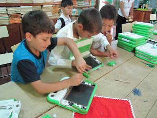 children working together to take apart a laptop, in Paraguay
