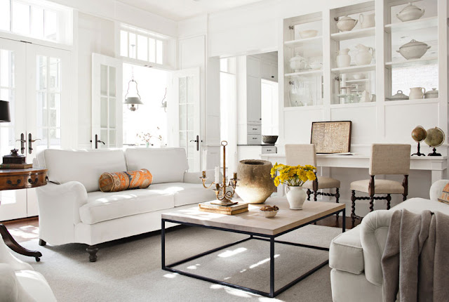 White living room with dueling sofas, turned wood chairs, french doors and ironstone dishware in the built in shelving