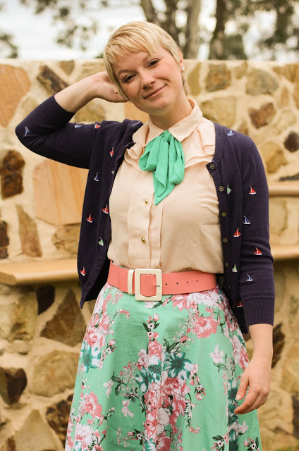 Liana of Finding Femme wears Modcloth pussy bow blouse, mind and pink floral Modcloth midi skirt, bubblegum pink bettie page heel, pink Alannah Hill belt, navy Laura Ashley embroidered sailboat cardigan.