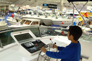 LA Boat Show child at ship steering wheel