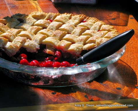A cherry pie with lattice crust sitting on a sunny table