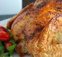 Foto de um frango assado de ótima qualidade, suculento com pimentas na decoração.