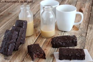 Foto de la receta anterior de barritas de brownie, rellenas de caramelo y almendra crujiente y cubiertas de chocolate , sobre una mesa de madera con unas tazas y unas botellitas de cristal con caramelo líquido.