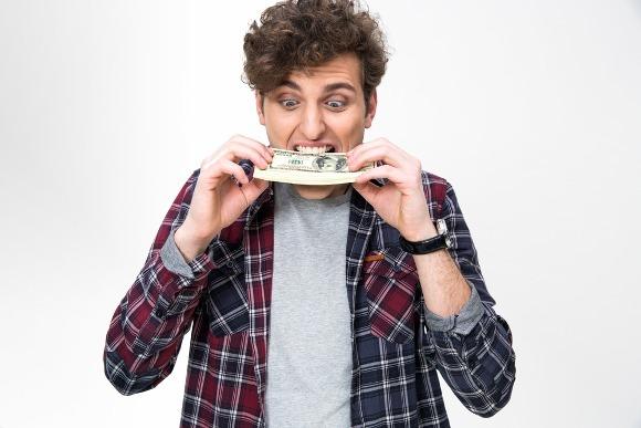 man biting stack of bills