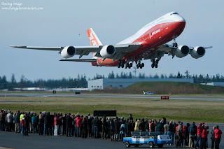 Boeing 747-8 Intercontinental Sunrise Red Livery lifts off in front of onlookers from runway 34L Paine Field for its first flight