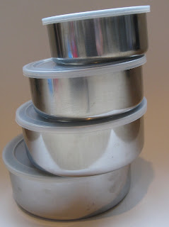 4 metal bowls with plastic lids stacked