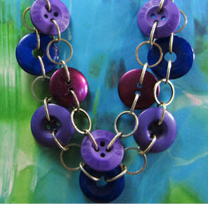 Double strand necklace has purple and blue buttons linked with silver chain loops and rings