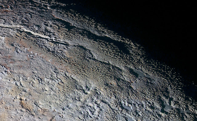 In this extended color image of Pluto taken by NASA's New Horizons spacecraft, rounded and bizarrely textured mountains, informally named the Tartarus Dorsa, rise up along Pluto's day-night terminator and show intricate but puzzling patterns of blue-gray ridges and reddish material in between. This view, roughly 330 miles (530 kilometers) across, combines blue, red and infrared images taken by the Ralph/Multispectral Visual Imaging Camera (MVIC) on July 14, 2015, and resolves details and colors on scales as small as 0.8 miles (1.3 kilometers).   Credit: NASA/Johns Hopkins University Applied Physics Laboratory/Southwest Research Institute