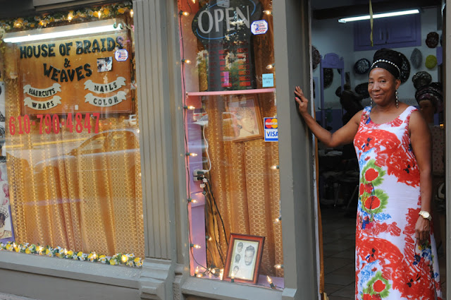 Debra Markowski stands in the doorway of her shop, Hair Braids and