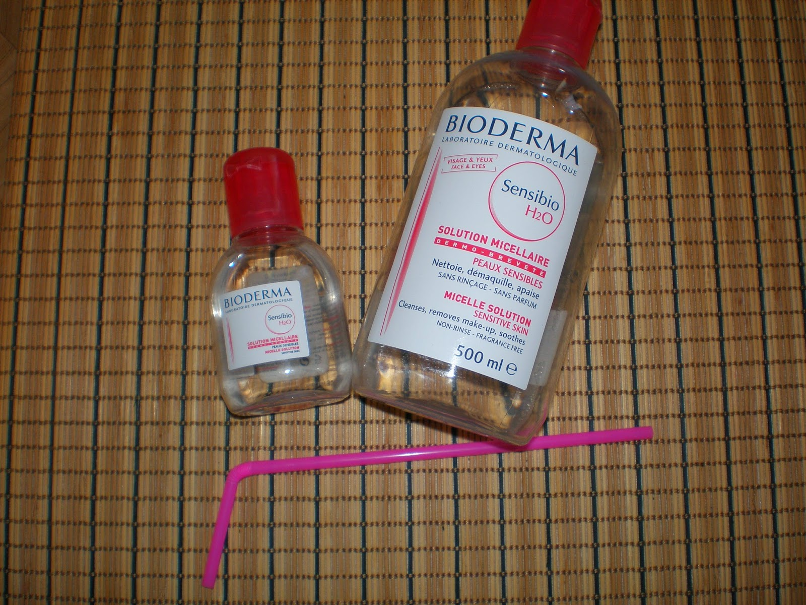 Large and small bottle of Bioderma and a straw