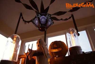Night photo of glowing vintage-style Halloween lantern (The Horrid Decor #2 Pus & Bruise on Ghost Skin) by Bindlegrim hanging over a authentic vintage paper Jack O'Lantern pumpkin