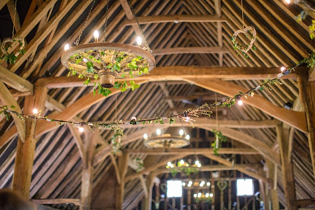 Rustic wedding venue decor + ivy and festoon lighting