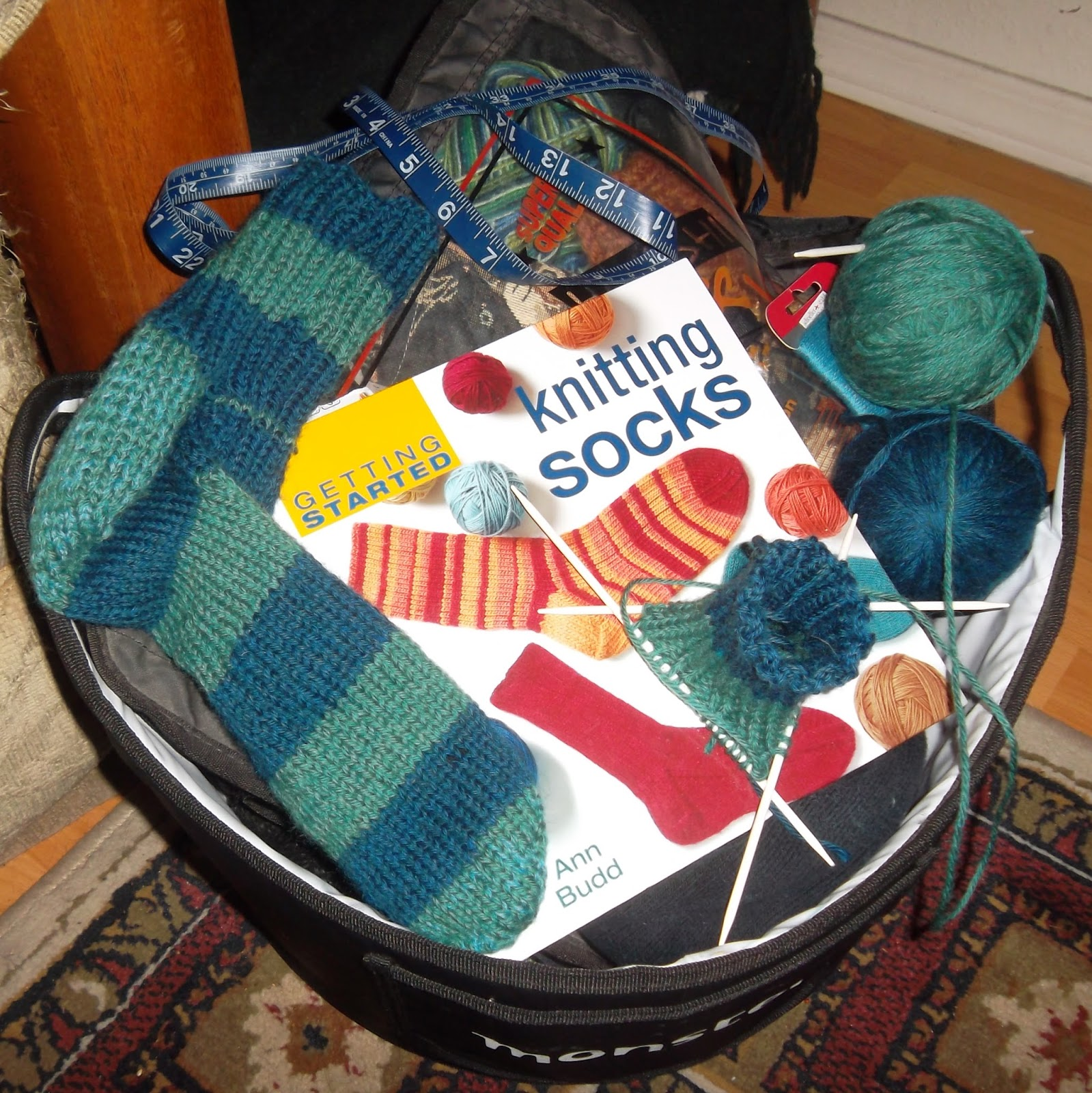Black work basket containing dark-and-light teal-striped sock, the leg of a second sock on double-pointed knitting needles with balls of dark and light teal yarn. With them is a book by Ann Budd, Getting Started Knitting Socks.