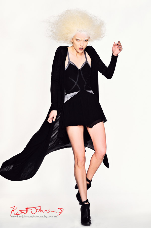 white background studio photography fashion campaign black dress and capewith movement