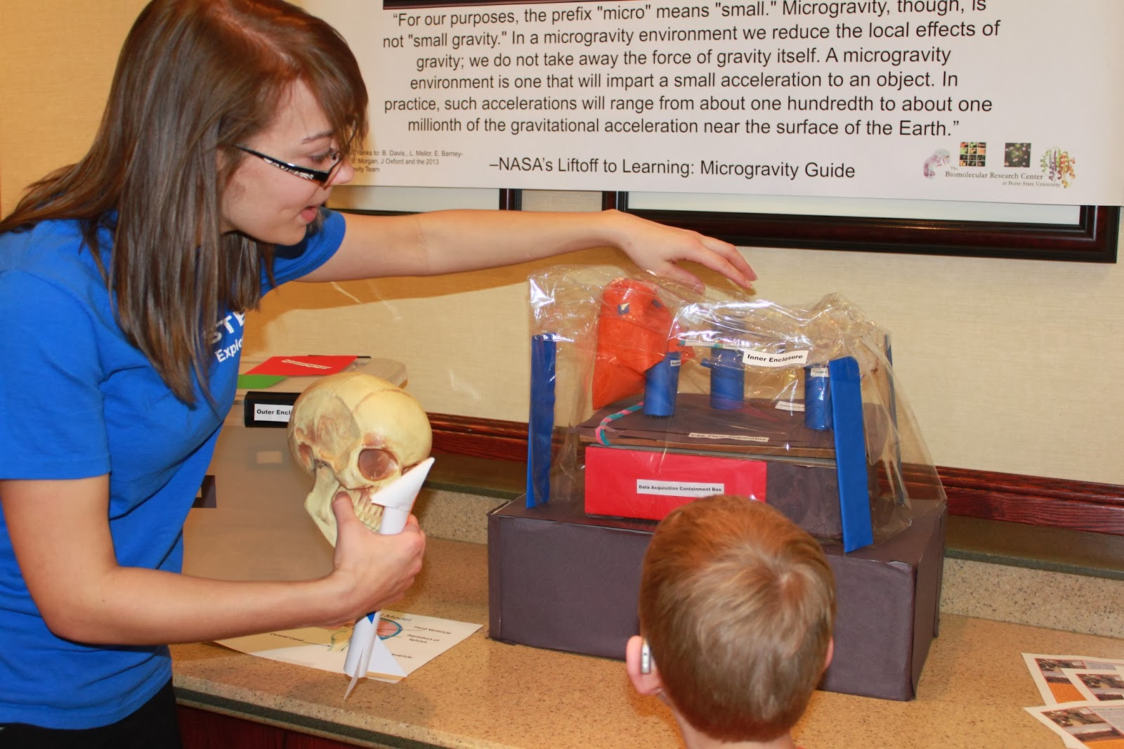 student showing kid an experiment at convention