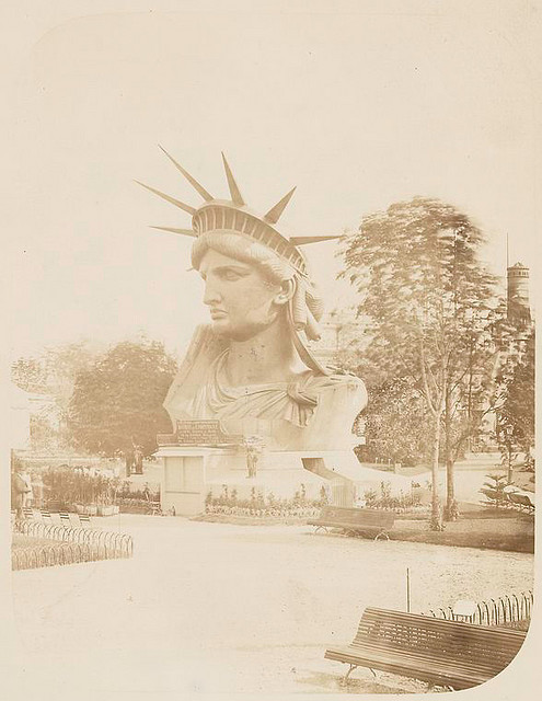 [Head of the Statue of Liberty on display in a park in Paris.]. Fernique, Albert -- Photographer. 1883. Source: Album de la construction de la Statue de la Liberte. Repository: The New York Public Library. Photography Collection, Miriam and Ira D. Wallach Division of Art, Prints and Photographs.