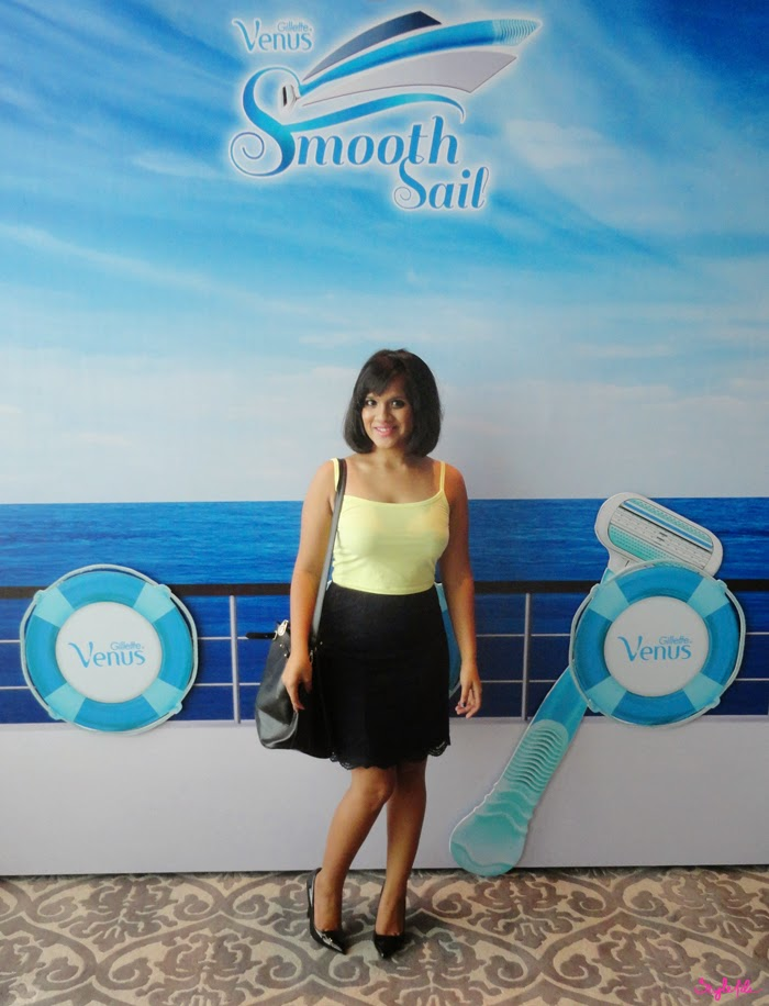 Dayle Pereira of Style File India wears a yellow crop top and blue lace pencil skirt with pumps and a handbag as she posses in front of the Gillette Venus press board