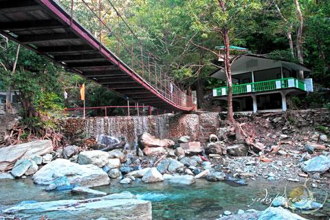 Hanging bridge and main cottage used my visitors at Calawagan
