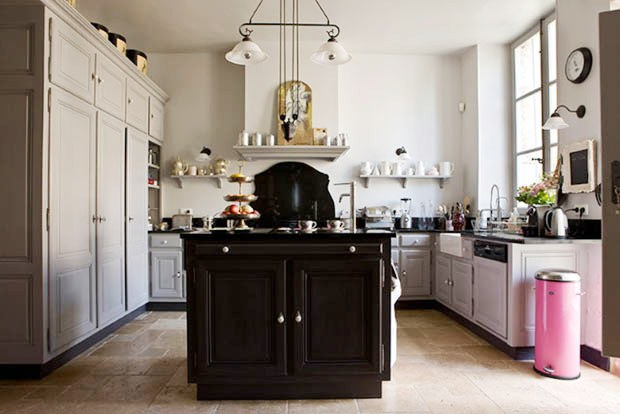 Kitchen in a french mansion with a black island, grey cabinets and drawers, a chandelier, black counter tops, a stone tile floor and a pink trash can