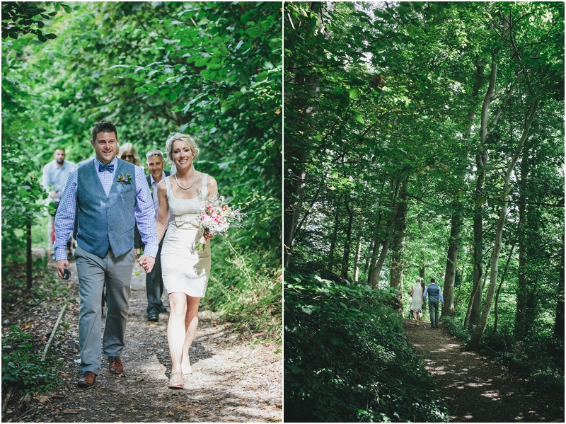 Bride and groom walk up through woods to Greenway House