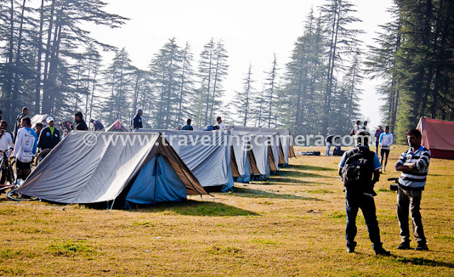 During recent trip in Himalayas, we also visited a small village called Ghda Kuffer with amazing natural beauty. We reached this place after crossing various hills, raw roads and dense forests, but all was worth... Let's have a quick Photo Journey of this place in Shimla region of Himachal Pradesh...This was our camping ground. It was actually a natural ground in the middle of dense forest with high cedars and pine trees. Although it was just beginning of October, but it was too cold out there. Weather made our experience more interesting :)Tents were installed all over Ghada Kuffer. This place was not close to the village but very approachable. There are 3-4 shops in the village for regular stuff. It was around 10 minutes walk to these shops and a beautiful water pond in the middle of Ghada Kuffer Market.As we start moving towards Ghada Kuffer village or market, the camp ground looked more beautiful. It was a climb from camping ground to Ghada Kuffer Market, although not very steep. For some of us it was easy and few of u were not very comfortable in taking short-cuts, so a dedicated road was also there which takes 10 minutes extra...Ghada Kuffer resident with typical Himachali Cap. Usually this cap can be seen in upper Himachal region, but at some places natural flowers are also added on top of it. And it's really surprising that flowers looks almost fresh all the time, unless cap is kept under pressure.A water pond near Ghada Kuffer Market... There are Various houses around this pond and folks in the village are mainly dependent on agriculture and Apple business. Although not everyone has Apple business.There are lot of such beautiful places in Hills of Himachal Pradesh and state of India, but least explored. Many time Himachal Tourism visited this place for analyzing the scope of tourism, but nothing happened till. This is what villagers told us.In past some of the folks also constructed their houses in a way that later, one portion can be converted into Guest-house under new home-stay scheme by Himachal Pradesh Tourism department.Kids following the lines...The very good part about villages in Himachal is about their thoughts around education. It's very hard to locate any child who is not going to schools and most of them do metric at least. Himachal Pradesh is one of the top 3 states in India, when we talk about Literacy.A view of hills around Ghada Kuffer Village, although this photograph is clicked when we left the village and moved towards Shilaroo.With this, PHOTO JOURNEY to Ghada Kuffer ended and hope to visit more such unexplored places in different states India and share on this blog !!!